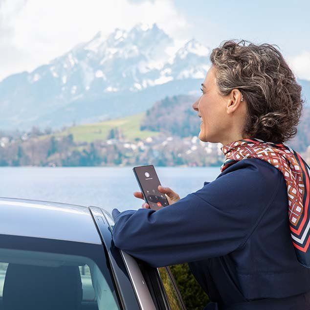 Woman wearing Bernafon Alpha rechargeable hearing aids stands by car at a Swiss lake and streams phone call from smartphone