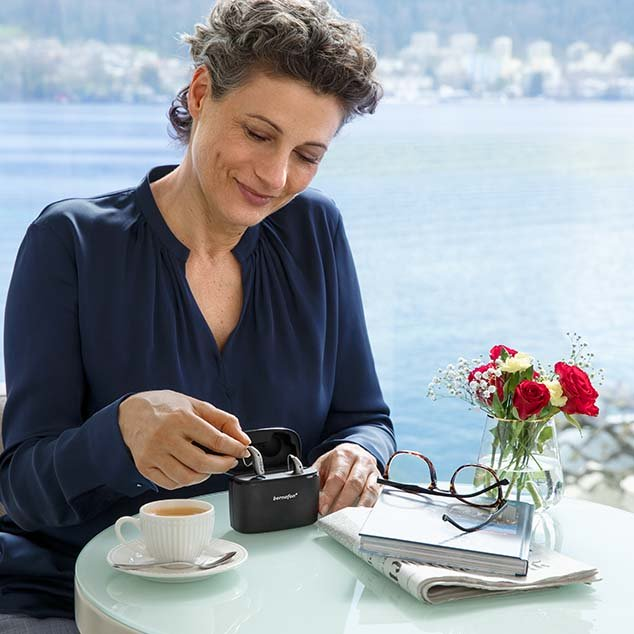 Woman sits at a table with Swiss lake view and removes Bernafon Alpha rechargeable hearing aids from portable Charger Plus