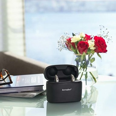 Bernafon Alpha rechargeable hearing aids in portable Charger Plus on a glass table with red flowers, a book and glasses