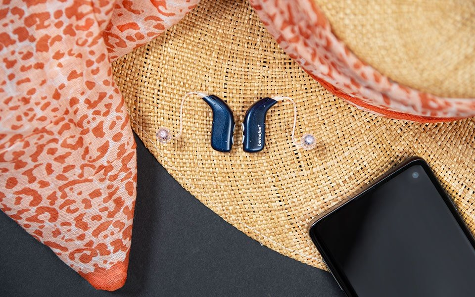 Midnight blue Bernafon Alpha rechargeable hearing aids placed next to a smartphone on a straw hat with animal print scarf