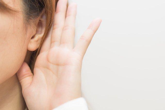 耳に手を当てる女性