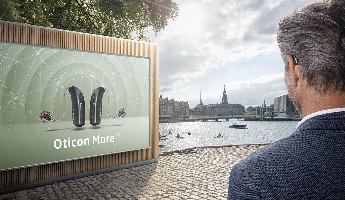 oticon_more_man-with_billboard_pma-1200x695