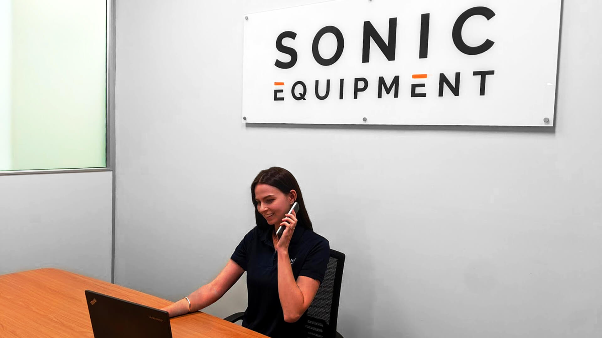Woman making a phone call sitting behind a desk in Sonic Equipment office